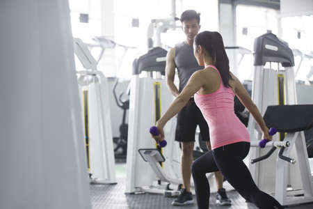 legs apart: Young woman working with trainer at gym