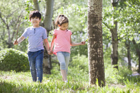 Happy children holding hands walking in woods LANG_EVOIMAGES