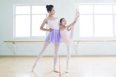 girl in full growth: Young ballet instructor teaching girl in ballet studio