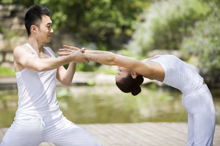 legs apart: Yoga instructor helping woman with pose