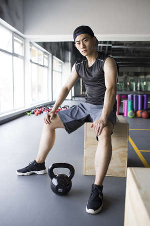legs apart: Young man sitting at gym LANG_EVOIMAGES