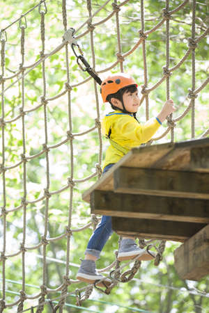 clambering: Little boy playing in tree top adventure park LANG_EVOIMAGES