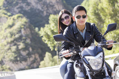 Young Chinese couple riding motorcycle together