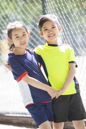 chainlink fence: Happy girls in sportswear LANG_EVOIMAGES