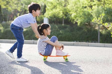 Little boy pushing girl on skateboard