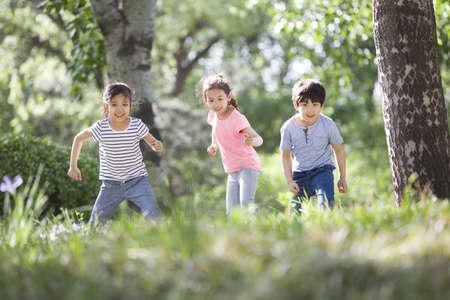 girl in full growth: Happy children racing in woods LANG_EVOIMAGES