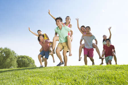Cheerful young adults playing on grass