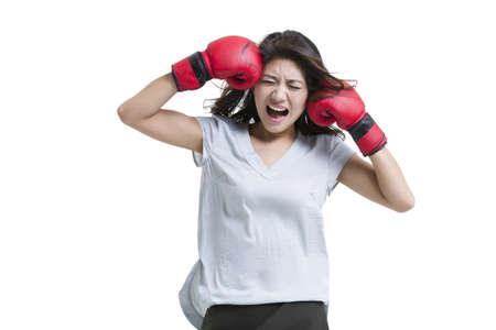puños cerrados: Joven mujer gritando con guantes de boxeo LANG_EVOIMAGES