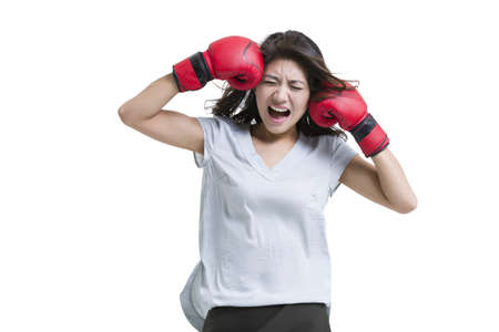 Young woman shouting with boxing gloves