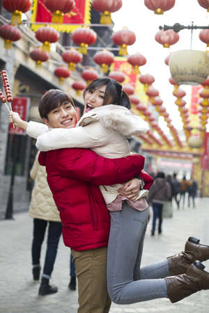 incidental people: Young couple with candied haw berries celebrating Chinese New Year LANG_EVOIMAGES