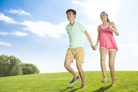 Cheerful young couple holding hands running on grass