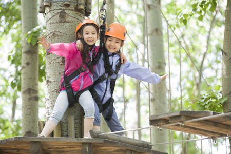 Little girls playing in tree top adventure park