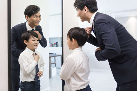 executive apartment: Father and son getting dressed in the morning LANG_EVOIMAGES