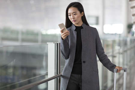 Businesswoman holding a smart phone in airport