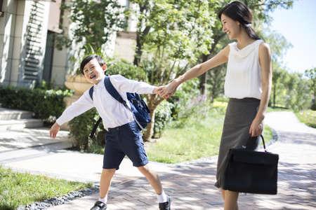 niños saliendo de la escuela: Mother taking her child to school in the morning
