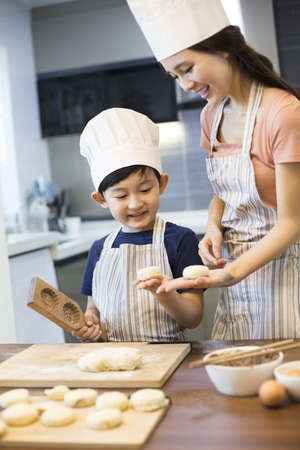 moulding: Happy young mother and son baking together