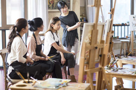 legs crossed at knee: Art teacher with young women in studio
