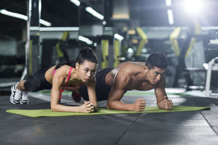 plank position: Young couple exercising at gym LANG_EVOIMAGES