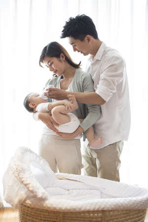 three generation: Young parents feeding baby