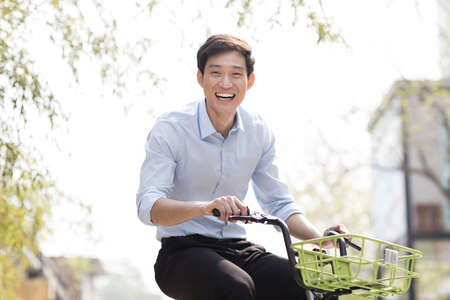 Young man riding a share bike LANG_EVOIMAGES