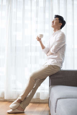 open windows: Cheerful young man drinking coffee at home