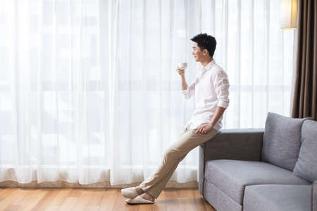 Cheerful young man drinking coffee at home