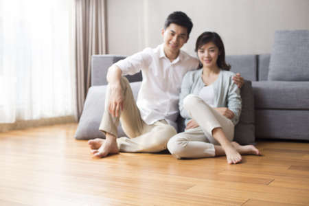 Happy young couple sitting on wooden floor