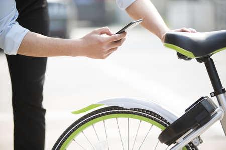 Young man scanning a QR code to unlock a share bike