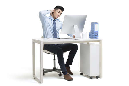 Tired young Chinese businessman working in office