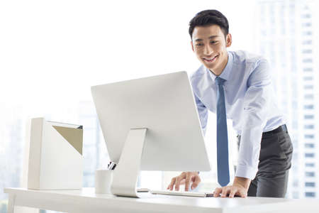 Young Chinese businessman using computer in office