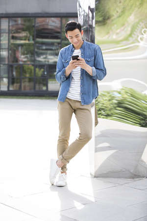 Young Chinese man using smart phone