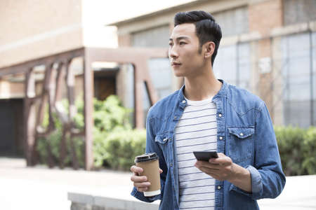 Young Chinese man holding a cup of coffee and a smart phone LANG_EVOIMAGES