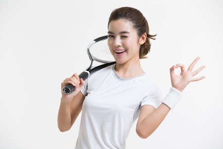 Young Chinese woman posing with tennis racket LANG_EVOIMAGES