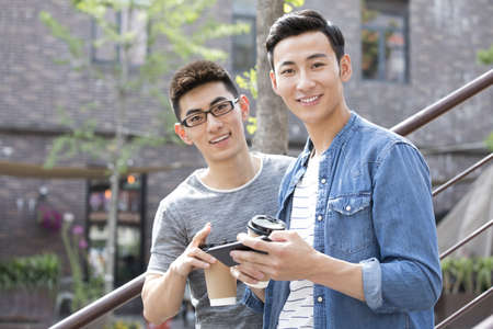 Young Chinese men having coffee break outdoors LANG_EVOIMAGES