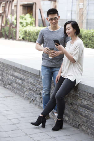 Young Chinese couple talking outdoors LANG_EVOIMAGES