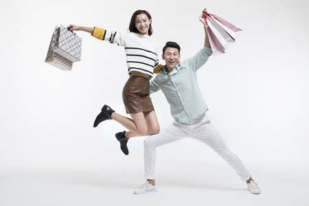 Cheerful young Chinese couple shopping