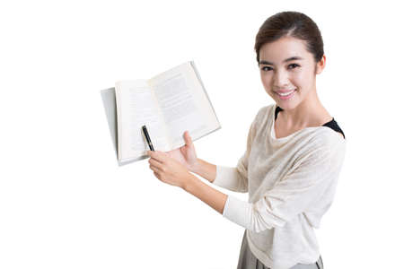 Young female Chinese teacher teaching with textbook