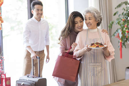 Young couple visiting their mother during Chinese new year LANG_EVOIMAGES