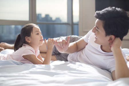 Cheerful young Chinese father making a pinky swear with his daughter on bed