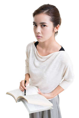 Serious young female Chinese teacher teaching with textbook
