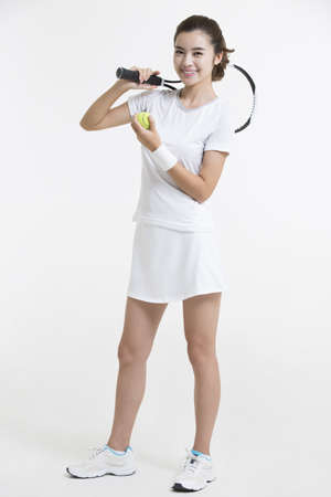 Young Chinese woman posing with tennis ball and racket