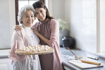 Cheerful Chinese mother and daughter making dumplings in kitchen