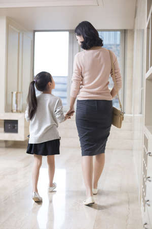 Young Chinese mother and daughter preparing to go out