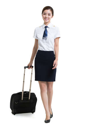 Smiling Chinese airline stewardess with wheeled luggage