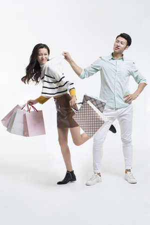 Humorous young Chinese couple shopping
