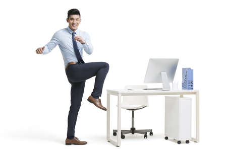 Young Chinese businessman exercising in office LANG_EVOIMAGES