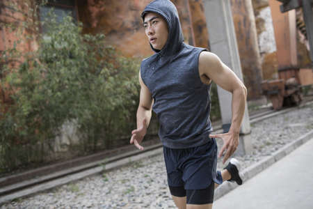 Young Chinese man jogging outdoors