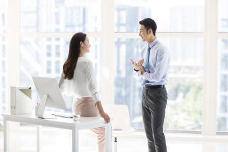 Confident Chinese business people talking in office