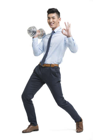 Young Chinese businessman lifting weights LANG_EVOIMAGES