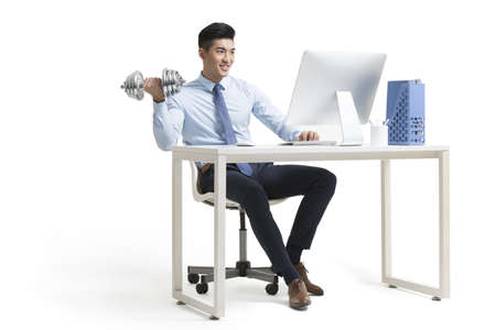 Young Chinese businessman lifting weights while using computer at work